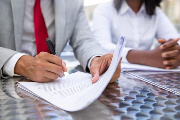 Colpo del primo piano dei documenti di firma dell'uomo d'affari
