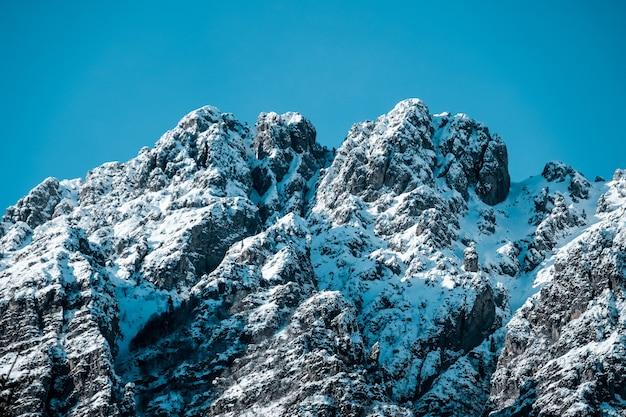 Colpo del primo piano dei picchi di montagna frastagliati innevati sotto i cieli blu liberi