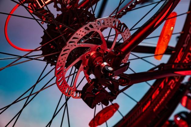 Colpo del primo piano del disco del freno nominato del meccanico sulla bicicletta nel lampo artificiale rosso