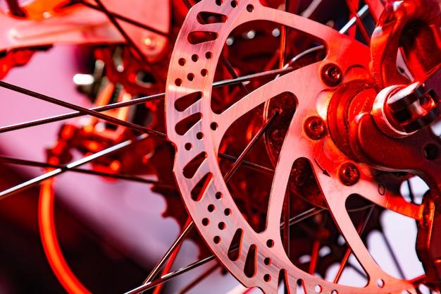 Colpo del primo piano del disco di freno nominato del meccanico sulla bicicletta in lampo artificiale rosso