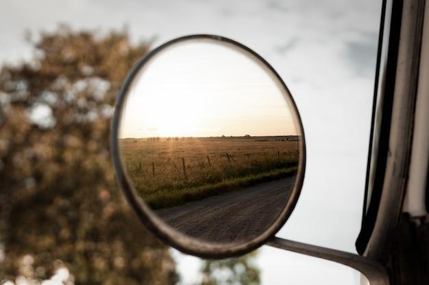 Colpo del primo piano del fuoco selettivo della vista di un campo di erba nello specchio laterale rotondo di un veicolo