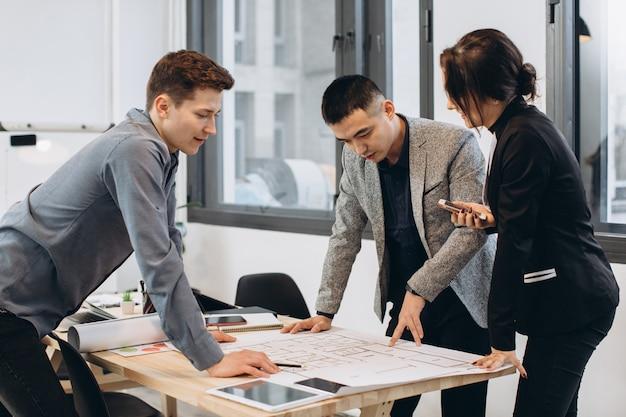 Colpo del primo piano del gruppo di architetti che riuniscono insieme piano dell'ufficio all'ufficio
