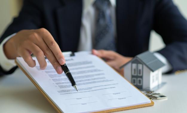 Colpo del primo piano del mediatore della camera che indica la penna sul documento che firma l'accordo di acquisto della casa.