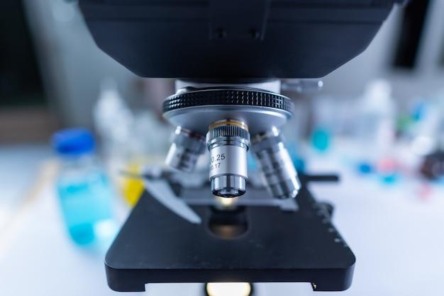 Colpo del primo piano del microscopio con la lente del metallo al laboratorio.