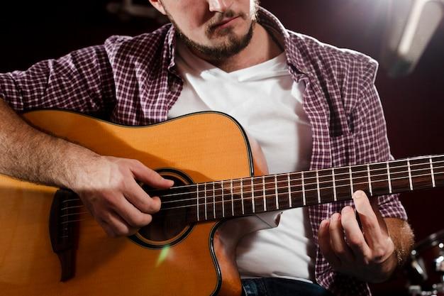 Colpo del primo piano del ragazzo a suonare la chitarra