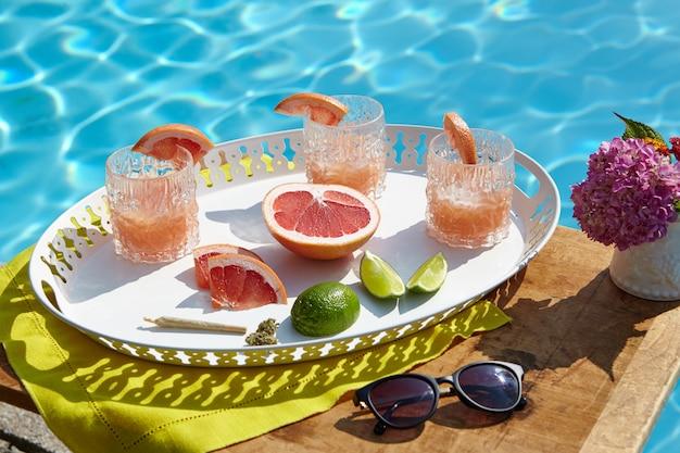 Colpo del primo piano dell'angolo alto di un vassoio con i cocktail del pompelmo vicino alla piscina