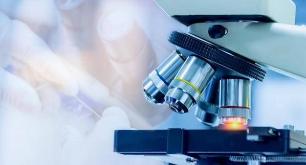 Colpo del primo piano dell'attrezzatura del microscopio con l'obiettivo di metallo al laboratorio microbiologico
