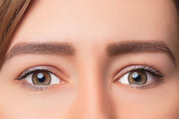 Colpo del primo piano dell'occhio della donna con trucco di giorno