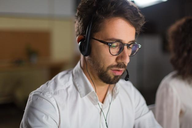 Colpo del primo piano dell'operatore sicuro della call center