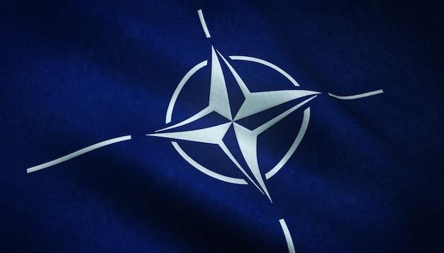 Colpo del primo piano della bandiera sventolante dell'organizzazione del trattato del nord atlantico con trame interessanti