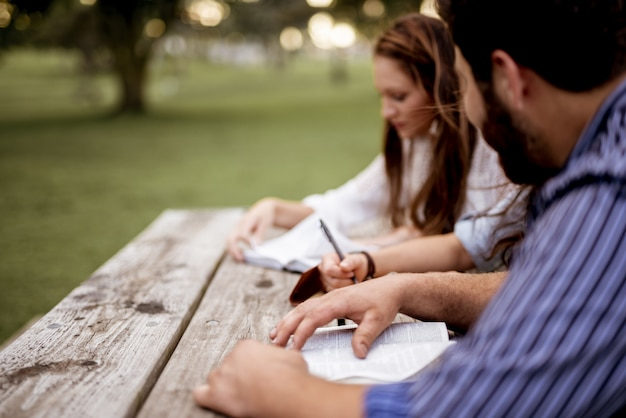 Colpo del primo piano della gente seduta nel parco e leggere la bibbia