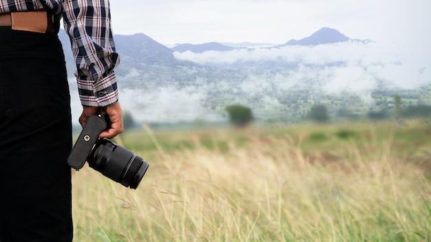 Colpo del primo piano della macchina fotografica della tenuta del fotografo che sta sul naturale verde