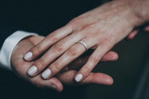 Colpo del primo piano della mano di una femmina con l'anello d'argento sulla mano di un maschio con uno sfondo sfocato