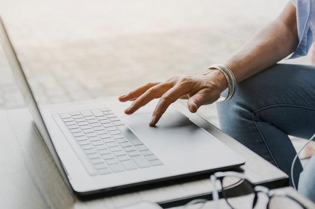 Colpo del primo piano della persona che per mezzo del computer portatile