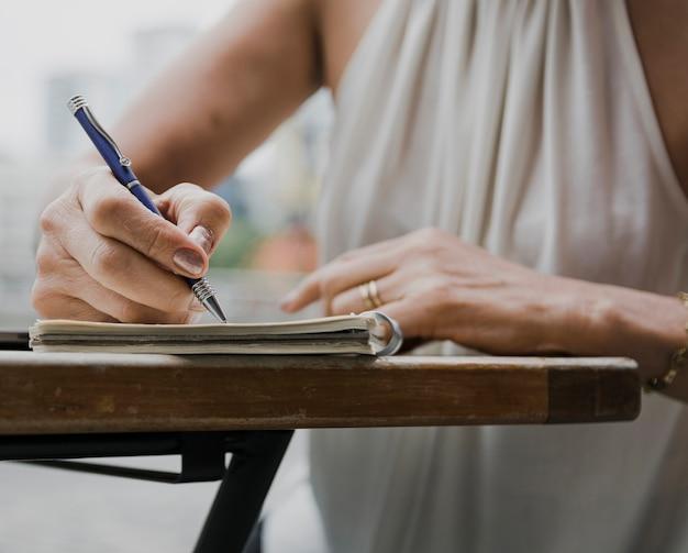 Colpo del primo piano della persona che scrive con una penna sul taccuino