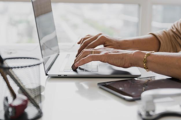 Colpo del primo piano della persona che scrive sul computer portatile