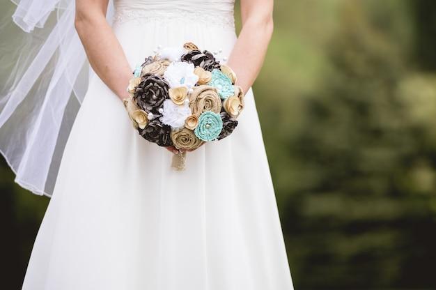 Colpo del primo piano della sposa che tiene un mazzo di fiori