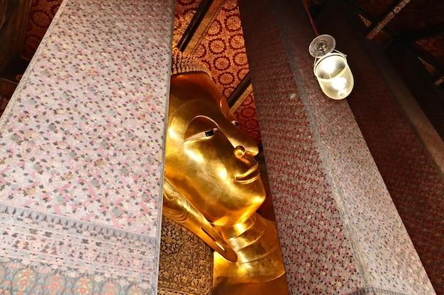 Colpo del primo piano della statua dorata del buddha nel complesso del tempio buddista di wat pho, tailandia