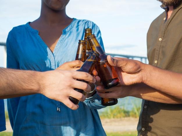 Colpo del primo piano delle bottiglie di birra tintinnanti degli amici. gruppo di giovani che si rilassano dopo il lavoro. concetto di celebrazione