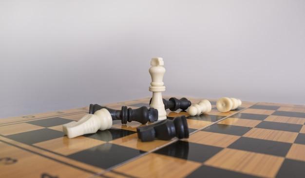 Colpo del primo piano delle figurine di scacchi su una scacchiera con uno sfondo bianco sfocato