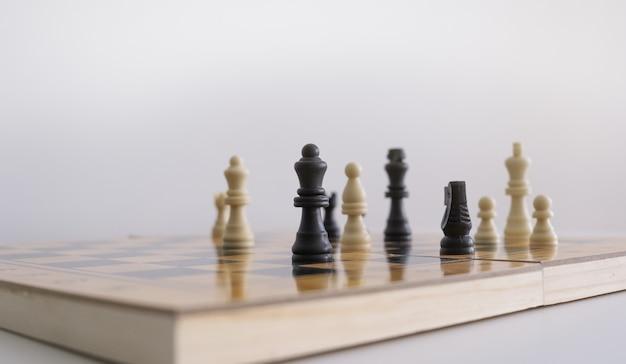 Colpo del primo piano delle figurine di scacchi su una scacchiera