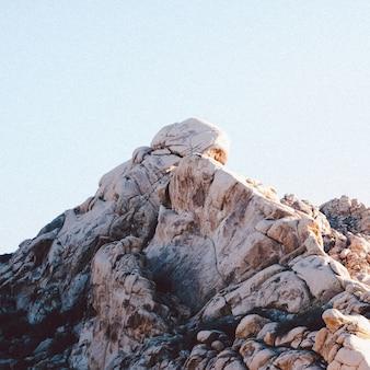 Colpo del primo piano delle formazioni rocciose sotto un chiaro cielo