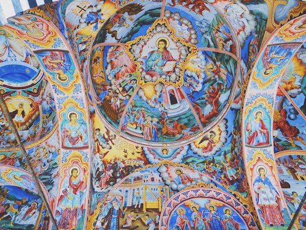 Colpo del primo piano delle immagini religiose cristiane sul soffitto delle pareti della chiesa