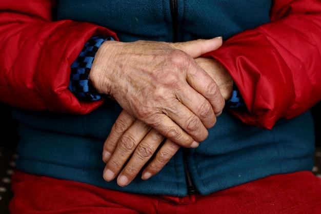 Colpo del primo piano delle mani rugose di una donna anziana