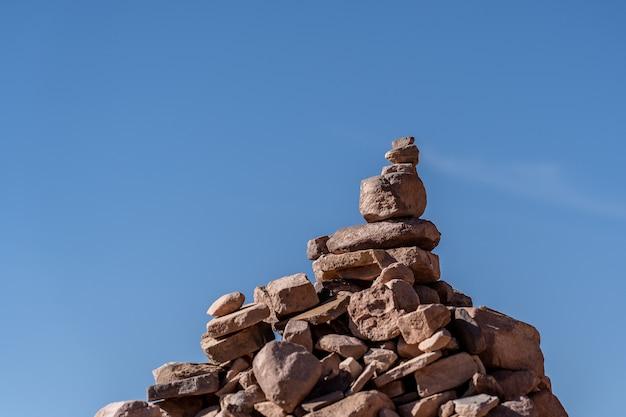 Colpo del primo piano delle pietre impilate l'una sull'altra con uno sfondo blu