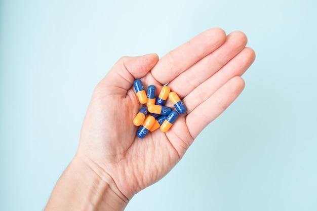 Colpo del primo piano delle pillole di un colore della tenuta della mano sul blu.