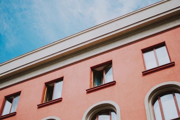 Colpo del primo piano di angolo basso di una costruzione rosa con le finestre
