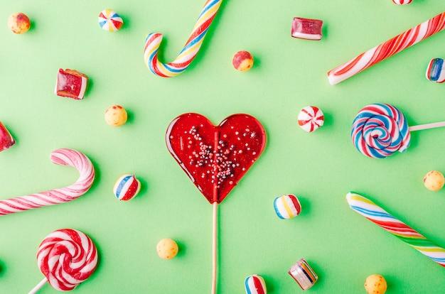 Colpo del primo piano di bastoncini di zucchero e altre caramelle su uno sfondo verde - perfetto per uno sfondo fresco