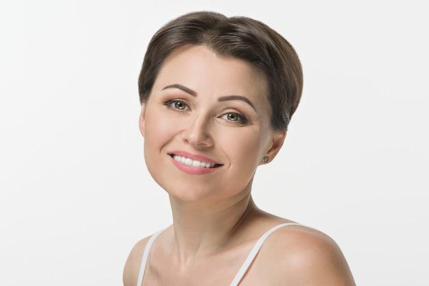 Colpo del primo piano di bella metà di donna adulta che sorride sul bianco