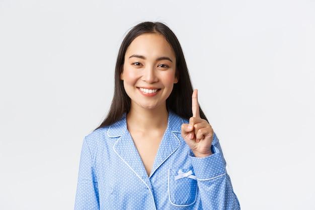 Colpo del primo piano di donna asiatica attraente felice in pigiama blu che mostra il numero uno, un dito e denti bianchi sorridenti, spiegare la regola o il concetto principale, muro bianco in piedi