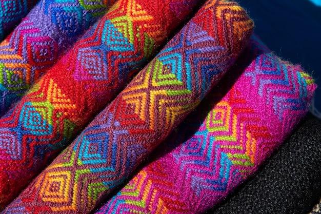 Colpo del primo piano di tessuti arrotolati con disegni colorati e unici