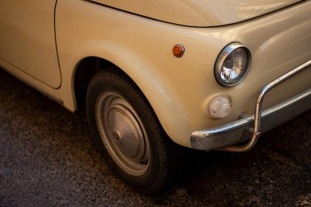 Colpo del primo piano di un'auto retrò bianca fredda parcheggiata sulla strada