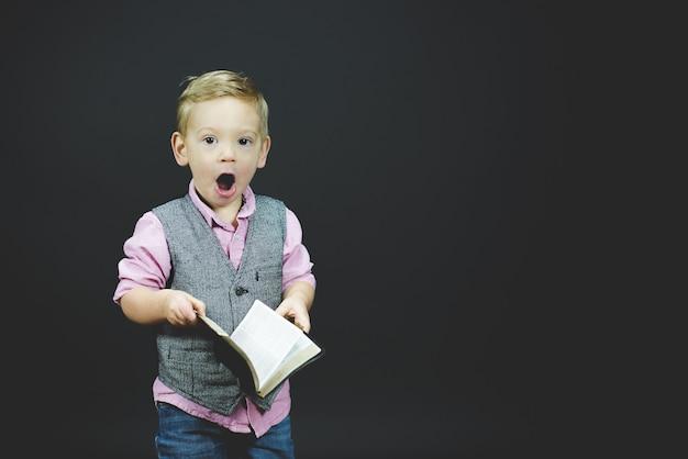 Colpo del primo piano di un bambino sorpreso che tiene la bibbia