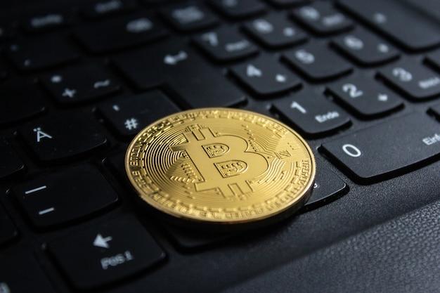 Colpo del primo piano di un bitcoin messo sulla tastiera di un computer nero