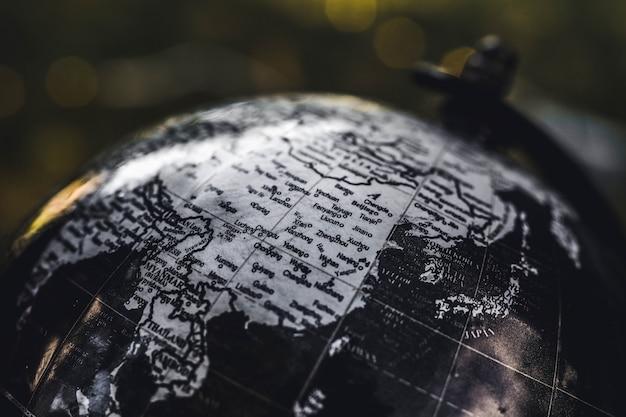 Colpo del primo piano di un globo di legno in bianco e nero con uno sfondo sfocato