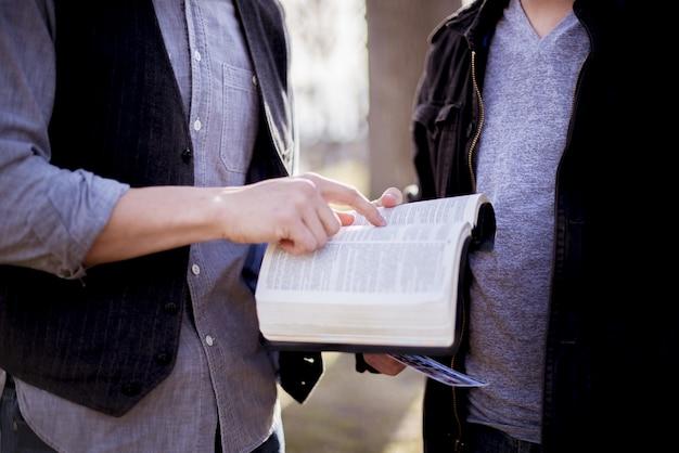 Colpo del primo piano di un maschio che indica una frase nella bibbia