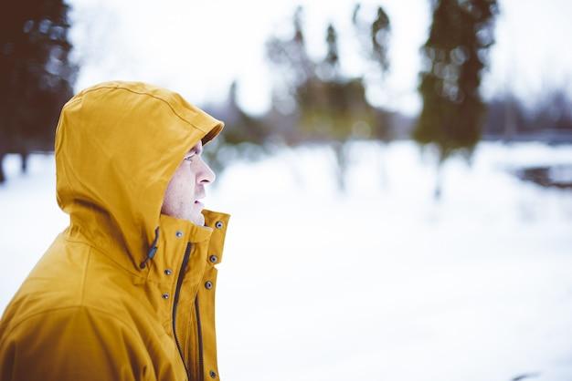 Colpo del primo piano di un maschio che indossa una giacca gialla invernale