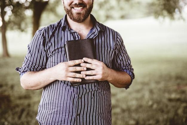 Colpo del primo piano di un maschio che sorride e che tiene la bibbia con una priorità bassa vaga