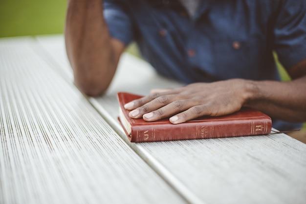 Colpo del primo piano di un maschio con la sua mano sulla bibbia su una tavola di legno