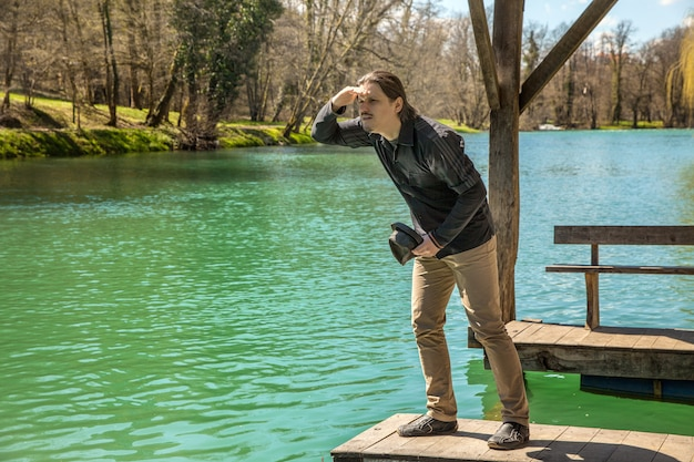 Colpo del primo piano di un maschio in piedi sul molo di legno vicino al lago e guardando l'orizzonte