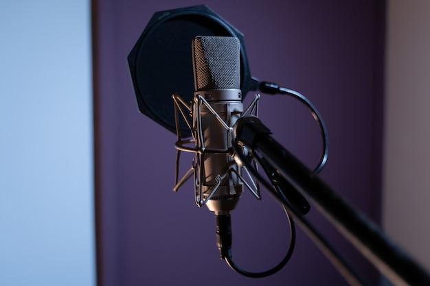 Colpo del primo piano di un microfono a condensatore con un filtro pop e uno sfocato