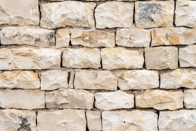 Colpo del primo piano di un muro di pietra bianca, un buon background