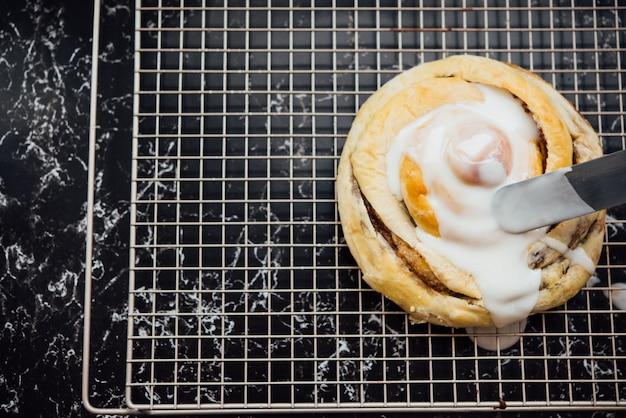 Colpo del primo piano di un panino di cannella con crema bianca