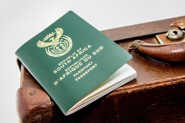 Colpo del primo piano di un passaporto sudafricano su un bagaglio marrone