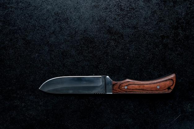 Colpo del primo piano di un piccolo coltello affilato con manico marrone su sfondo nero