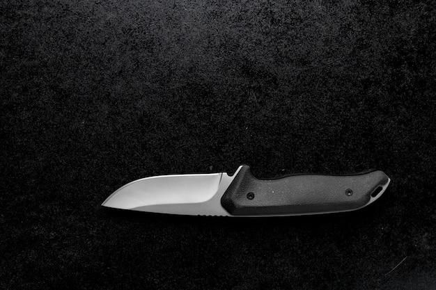 Colpo del primo piano di un piccolo coltello affilato con manico nero su sfondo nero